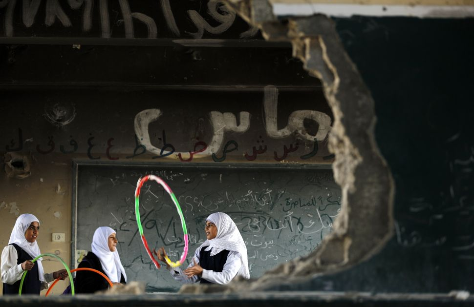 Palestinian girls play inside their school which was destroyed during the 50 days of conflict between Israel and Hamas in the