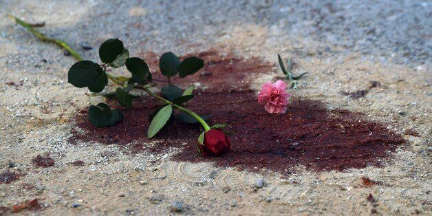 Roses are seen on bloodstains in front of the National Bardo Museum in Tunis on March 19, 2015 during a demonstration in soli
