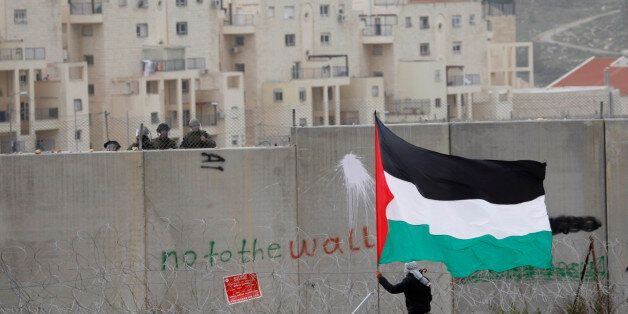A protestor waves a Palestinian flag in front of Israeli troops during a protest against Israel's separation barrier in the W