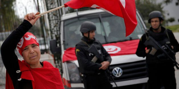 A woman waves the Tunisian flag as policemen stand guard at the National Bardo Museum two days after gunmen attacked the muse