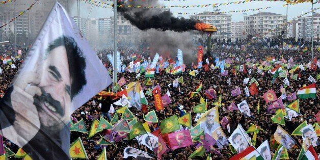 Smoke rises from a fire burning as people wave Kurdish flags and pictures of jailed Kurdish rebel leader Abdullah Ocalan as t
