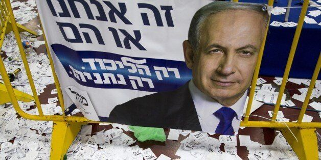 Copies of ballots papers and campaign posters for Israel's Prime Minister Benjamin Netanyahu's Likud Party lie on the ground