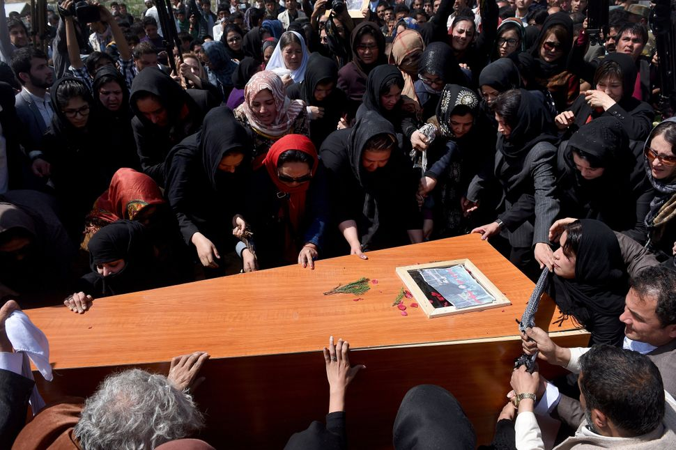 Independent Afghan civil society activist women and Afghan men lower the coffin of Afghan woman Farkhunda, 27, who was lynche