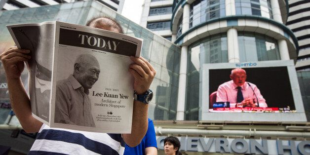 A monitor shows coverage of the death of Singapore's first elected Prime Minister Lee Kuan Yew as a man reads a special editi