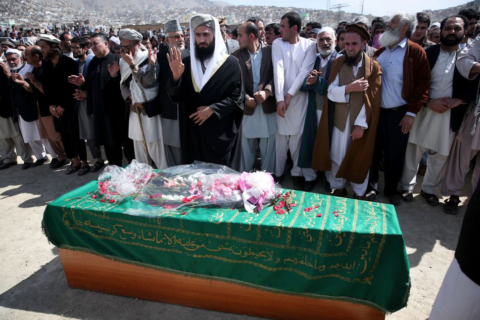 Civil society activists and relatives pray during the funeral of 27-year-old Farkhunda, an Afghan woman who was beaten to dea