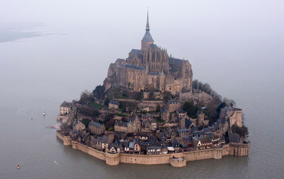 An aerial view as a high tide submerges a narrow causeway leading to the Mont Saint-Michel, on France's northern coast, Satur