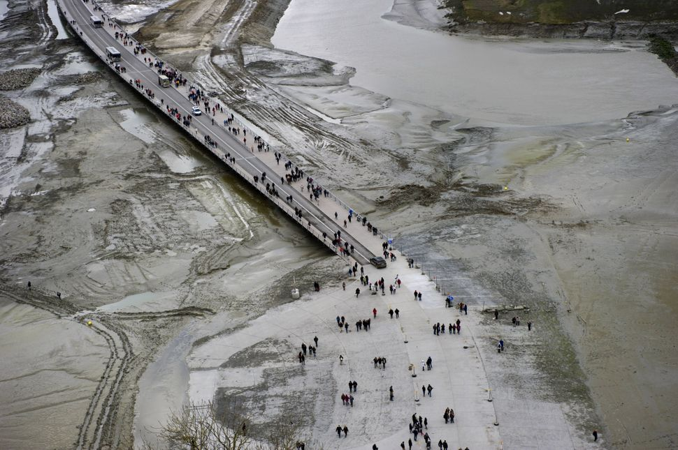 People wait for the wave named 'Mascaret' in front of the Mont-Saint-Michel, on March 21, 2015. Thousands of people flocked t