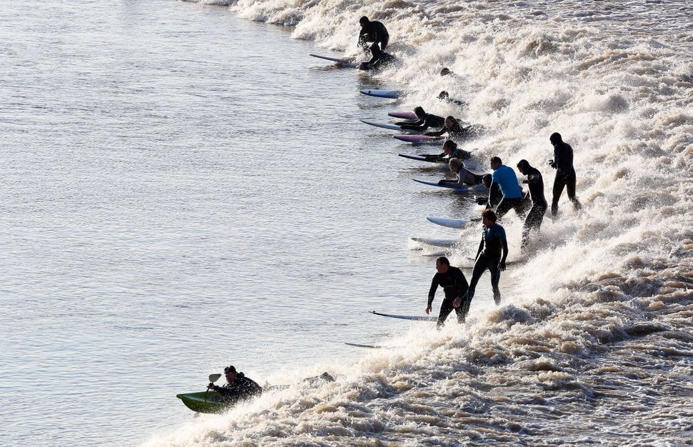 Surfers ride the wave of the tidal bore called Severn bore on the River Severn at Newnham in Gloucestershire, South West Engl