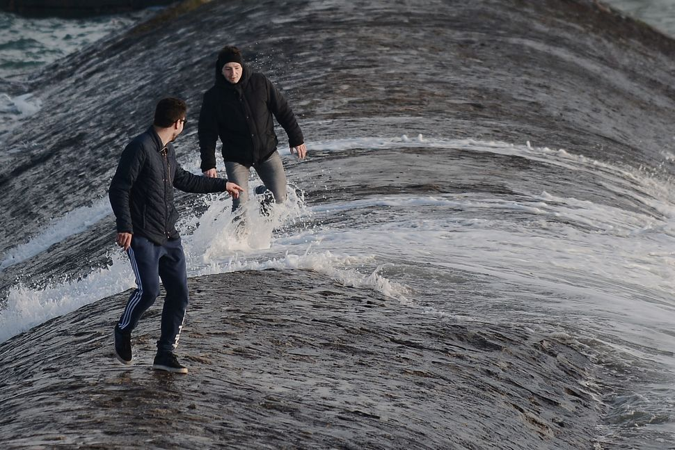 People watch the waves on the sea wall of the Port of Les Sables-d'Olonne, western France, during high tide on March 21, 2015