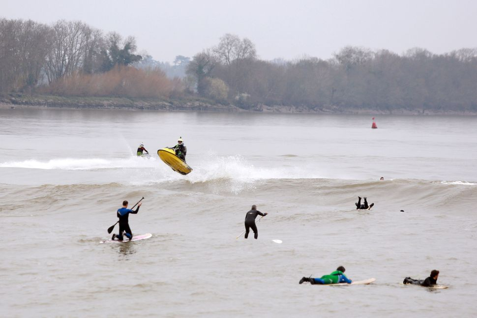 Men on paddle boards ride the tidal wave called 'mascaret' on March 21, 2015 in Vayres.