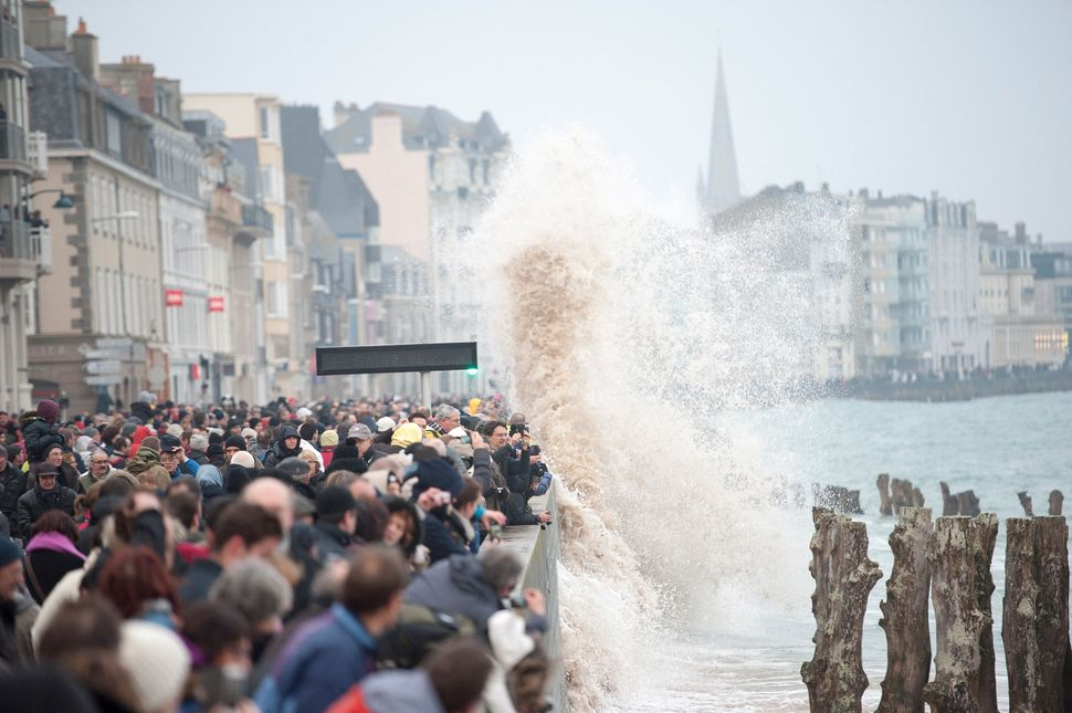 A wave rushes to the coast as people gather on the boardwalk in Saint-Malo coast for 'Tide Of The Century' on March 21, 2015