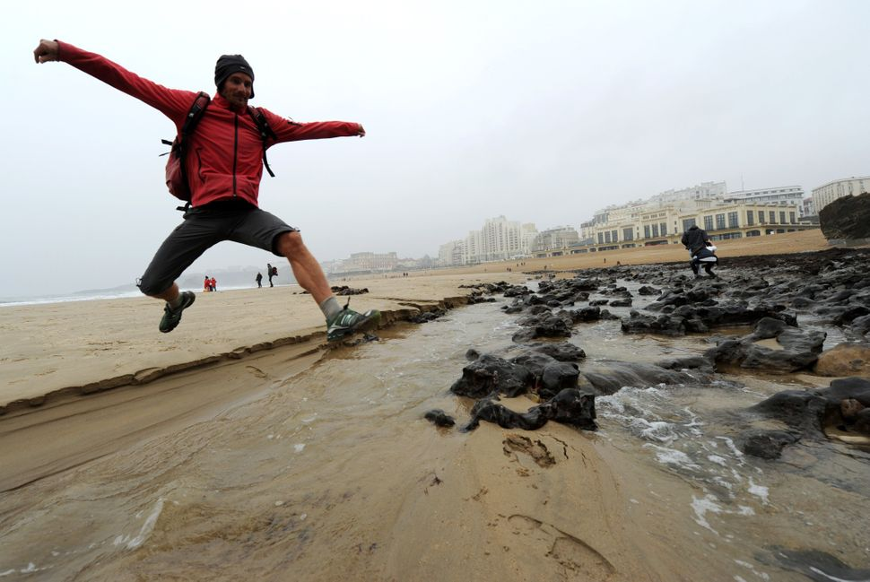 A man jumps above water at low tide on Biarritz' Great Beach, southwestern France, on March 21, 2015. France kicked off nearl