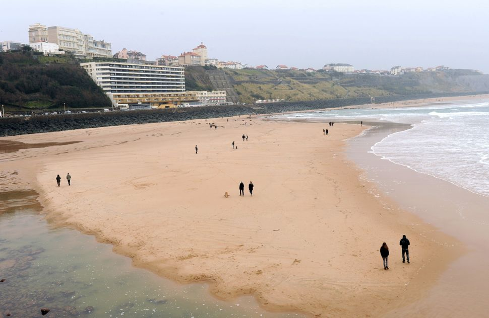 People stroll at low tide on Biarritz' beach, southwestern France, on March 21, 2015. France kicked off nearly a month of exc