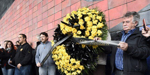 Employees of Barcelona's El Prat airport hold a wreath of flowers as they observe a minute of silence at noon to honour the v
