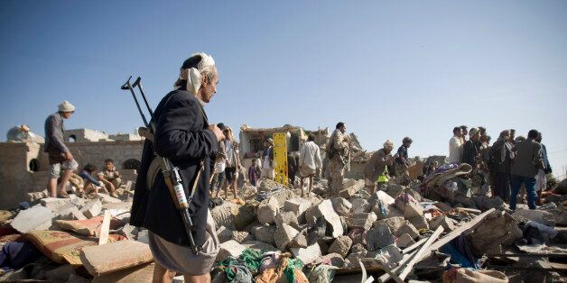 A Houthi Shiite fighter stand guard as people search for survivors under the rubble of houses destroyed by Saudi airstrikes n