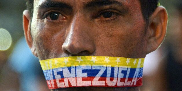 A man attends a protest against the government of Venezuelan President Nicolas Maduro in Caracas on February 23, 2014. A tota
