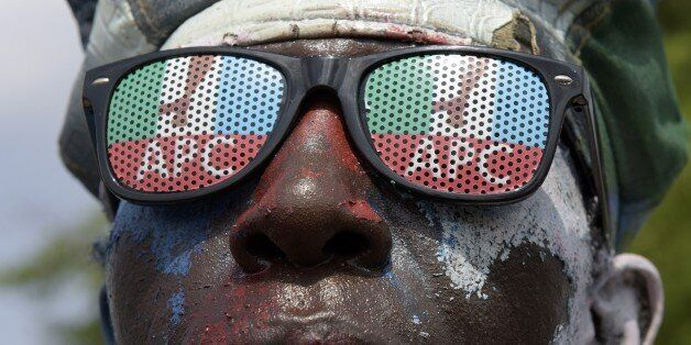 A man wears glasses adorned wit hthe logo of Nigeria's main opposition All Progressives Congress (APC) as residents await res