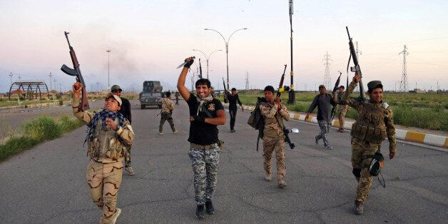 Iraqi security forces chant slogans against the Islamic State group as they open the main road between Baghdad and Tikrit, 80