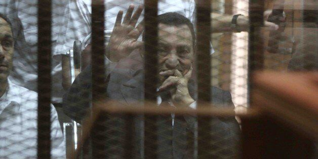 Egypt's deposed president Hosni Mubarak waves from behind the accused cage during his trial on May 21, 2014 in Cairo. An Egyp