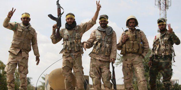 Shiite fighters from the Popular Mobilisation units flash the sign for victory in Tikrit on April 1, 2015, a day after the Ir