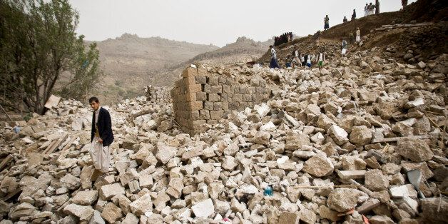 Yemenis stand amid the rubble of houses destroyed by Saudi-led airstrikes in a village near Sanaa, Yemen, Saturday, April 4,