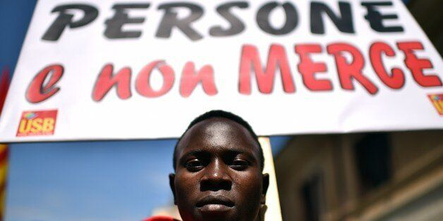 A demonstrator displays a placard which translates as 'We are People, no Goods' during a demonstration by asylum-seeking immi