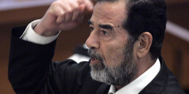 Baghdad, IRAQ:  Former Iraqi President Saddam Hussein gestures while addressing the court in Baghdad's heavily fortified Gree