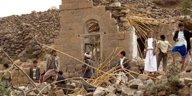Yemenis gather as they search for survivors in the rubble of houses destroyed by Saudi-led airstrikes in a village near Sanaa