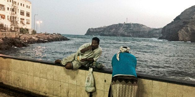In this Monday, March 16, 2015 photo, men chew qat, a mildly narcotic leaf, by the Arabian Sea coast in Aden, Yemen. Calls am
