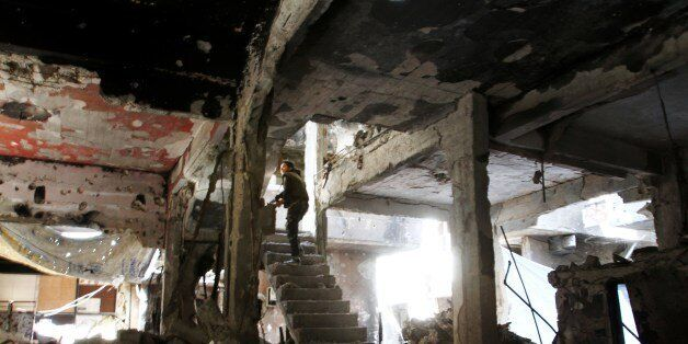 A man stands on a staircase inside a demolished building in the Yarmuk Palestinian refugee camp in the Syrian capital Damascu