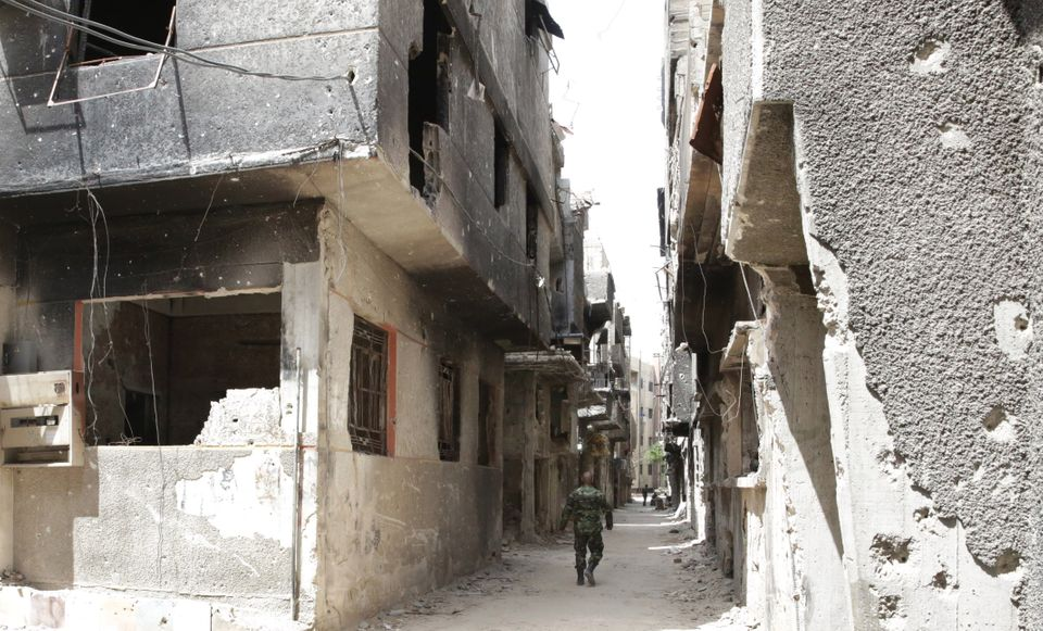 A soldier walks down an alley through heavy damage during a government escorted visit to Yarmouk refugee camp in Damascus, Sy