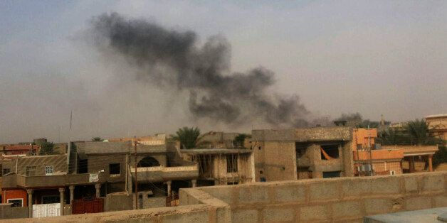 Smoke plumes are visible over buildings in the Iraqi town of Hit, in western Anbar province - 140 kilometers (85 miles) west