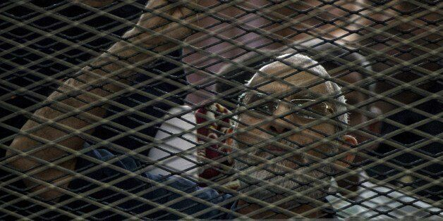 Egyptian Muslim Brotherhood leader Mohamed Badie gestures as he shouts from inside the defendants cage during his trial in th
