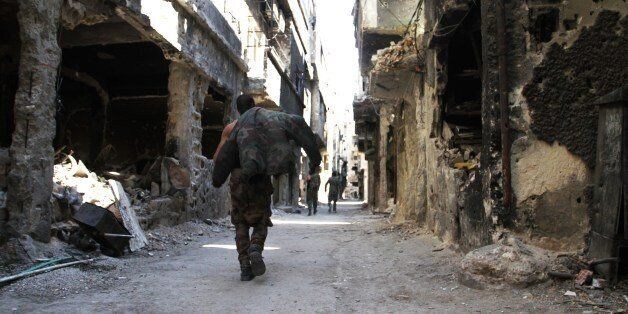 Men walk past destroyed buildings in the Yarmuk Palestinian refugee camp in the Syrian capital Damascus on April 6, 2015. Aro