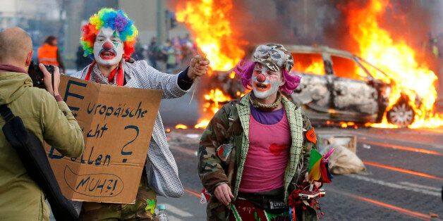Demonstrators dressed as clowns pass by a burning police car Wednesday, March 18, 2015 in Frankfurt, Germany. The Blockupy al