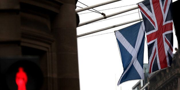 A Saltire and Union Jack flag hang side by side on a building in Edinburgh, Scotland, Friday, Sept. 19, 2014. Scottish voters