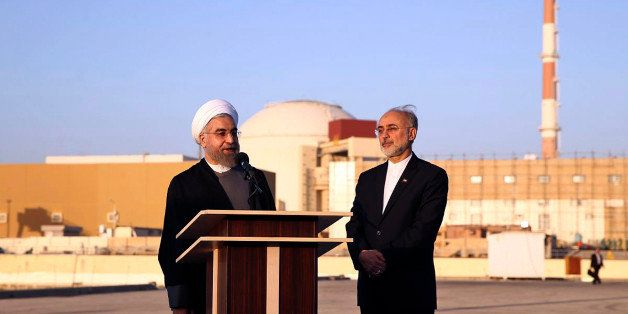 In this photo released by the Iranian Presidency Office, President Hassan Rouhani, left, speaks as he is accompanied by the h