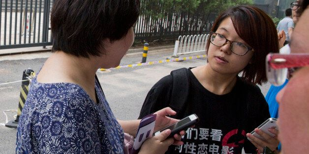 In this photo taken Thursday, July 31, 2014, women's rights activist Wei Tingting, right, waits outside a court where the fir