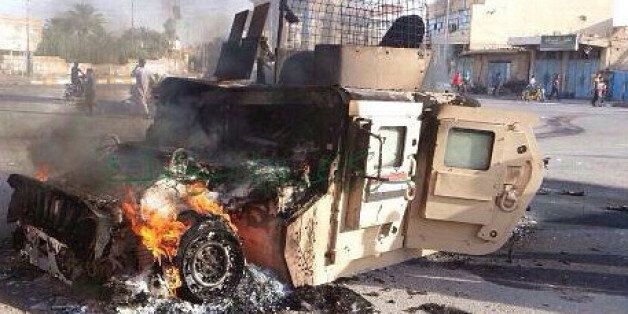 In this Sunday, Oct. 5, 2014. photo, an Iraqi military vehicle burns after an attack by the militant Islamic State group, in