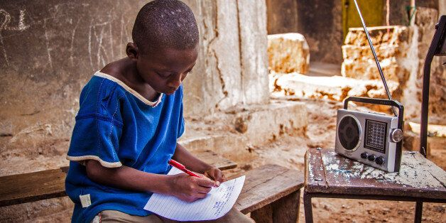 In this photo taken on Thursday, Feb. 26,  2015, a boy listens to school classes broadcast over the radio, due to the Ebola v