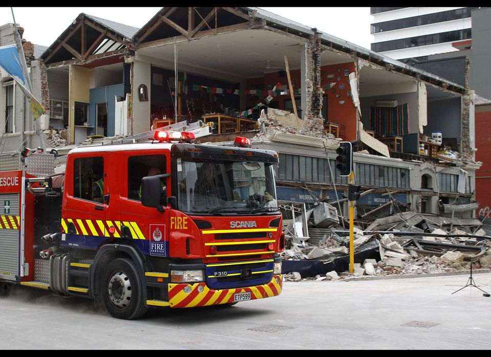Fire and Urban Search and Rescue personnel arrive at a destroyed building in Christchurch, New Zealand.