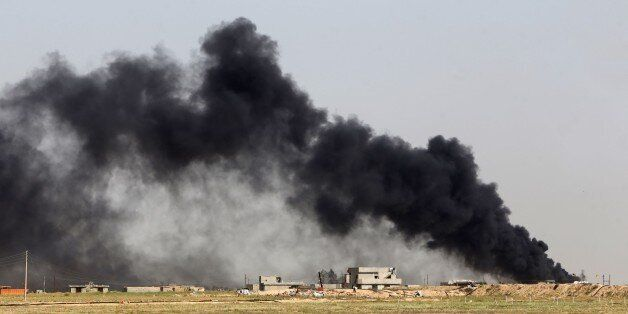 Smoke billows from what is believed to be an oil field which was set alight by Islamic State (IS) group militants in the Mkei