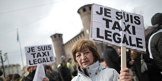 ItalianTaxi drivers hold placards reading 'Je Suis Taxi Legale' (I am a legal taxi) during a demonstration against minicabs a