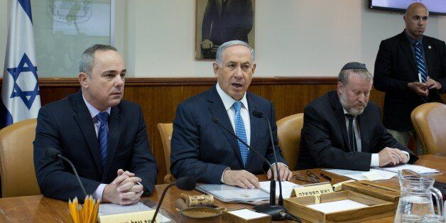 Israeli Prime Minister Benjamin Netanyahu (C) talks to the press during the weekly cabinet meeting, as he sits next to Yuval