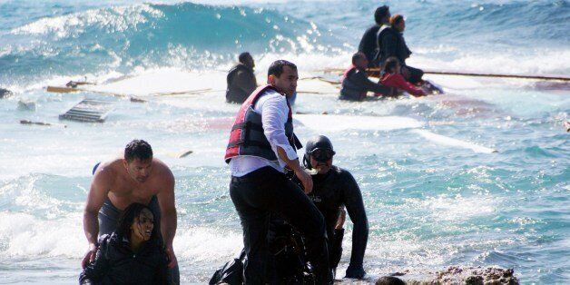 Local residents and rescue workers help a migrant woman after a boat carrying migrants sank off the island of Rhodes, southea