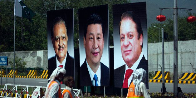 Municipality workers walk past a billboard showing pictures of Chinese President Xi Jinping, center, with Pakistan's Presiden
