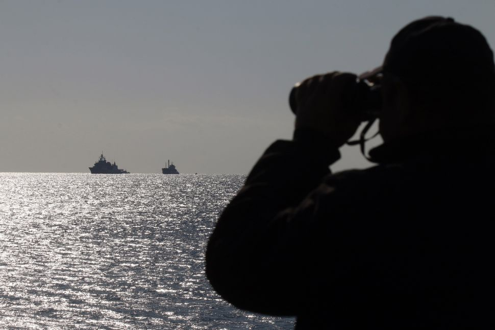 A coast guard officer looks at a navy ship towing a Kiribati-flagged ferry carrying some 700 migrants off the Cretan port of