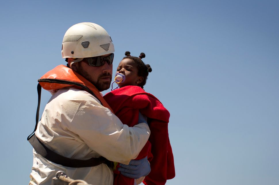 A rescue worker tends a young migrant girl in the port of Tarifa after she was rescued by a Spanish coast guard vessel on Aug