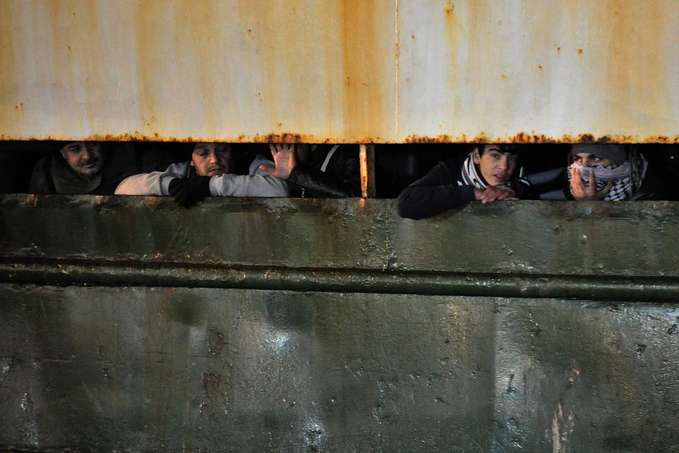 Some 500 Syrian migrants arrive aboard the Ezadeen ship in the harbor of Corigliano, Italy, on Jan.  2, 2015.