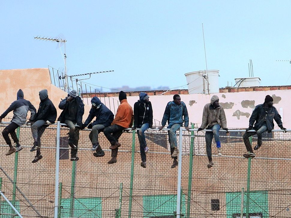 Migrants sit atop a border fence separating Morocco from the North African Spanish enclave of Melilla on Feb. 19, 2015.